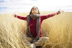 Joyful sunshine. Beautiful young woman enjoying sunshine in a field with long grass Stock Image