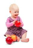 Joyful sweet baby in violet dress sits and apples Royalty Free Stock Image