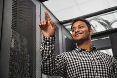 Joyful IT technician recounting server closet. Apparatus room. Low angle of positive IT technician standing in server room and counting royalty free stock photo