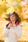 Joyful teen girl having fun in falling leaves. Joyful teen girl smiling and having fun in falling autumn leaves in a park royalty free stock photography