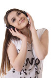 Joyful teen girl with headphones listens to the music. Over white Stock Image