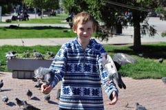 The joyful teenage boy feeds pigeons from hands Stock Photo