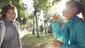 Joyful teenage caucasian girl blowing soap bubbles to her positive grandmother in the sunny autumn park. Family having. Fun on weekend. Good relashionship stock footage