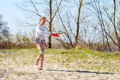 Joyful teenage girl, blonde playing with flying disk. While resting on the river bank on a sunny day - active weekend in nature Royalty Free Stock Photo