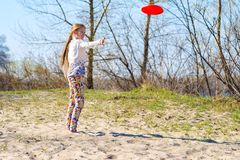 Joyful teenage girl, blonde is throwing flying disk. On the river bank on a sunny day - active weekend in nature Stock Photos