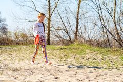 Joyful teenage girl, blonde is walking barefoot with flying disk. Along the river bank on a sunny day - active weekend in nature Royalty Free Stock Image