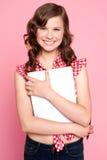 Joyful teenage girl holding spiral notebook. Educational concept Stock Images