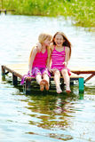 Joyful teenage girls. Two joyful teenage girls sit on wooden river bridge Stock Images