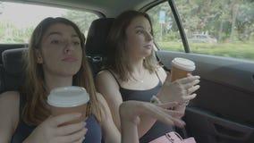 Joyful teenage girls going on vacation dancing and drinking coffee enjoying travel in a car stock video