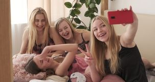 Joyful teenage girls taking selfie using mobile camera at slumber party stock video