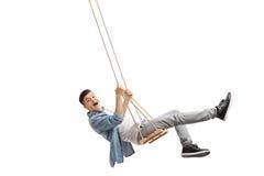 Joyful teenager swinging on a swing Stock Images