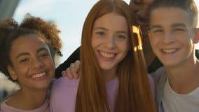 Joyful teenagers hugging female friend smiling on camera, adolescent wellness