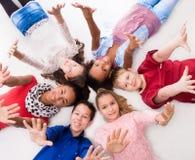 Joyful teenagers lying on the floor head to head Royalty Free Stock Image