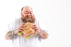 Joyful thick guy eating big bun with meat Royalty Free Stock Image