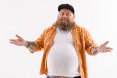 Joyful thick guy gesturing innocently. Fat bearded man is standing and stretching arms sideways. He is looking at camera with confidence. Isolated Royalty Free Stock Photos
