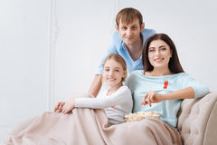 Joyful tolerant family supporting AIDS prevention campaign. We are for health. Joyful tolerant close knit family sitting together and wearing red ribbons while Royalty Free Stock Photos