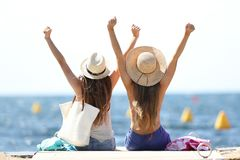 Joyful tourists on summer vacations on the beach. Back view of two joyful tourists raising arms sitting on a pier on summer vacations on the beach stock photography