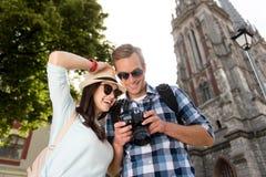 Joyful tourists watching photos in the camera Royalty Free Stock Photos