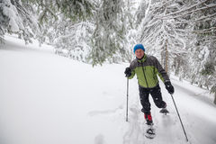 Joyful traveler running snowshoeing in deep snow Stock Photos