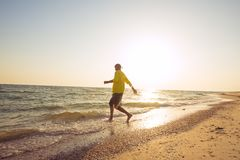Joyful traveler runs to the sea Royalty Free Stock Photo