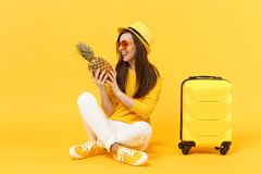 Joyful traveler tourist woman in summer clothes, hat hold fresh ripe pineapple fruit isolated on yellow orange. Background. Passenger traveling abroad on royalty free stock photography