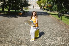 Joyful traveler tourist woman in yellow clothes, hat sitting on suitcase holding city map search route in city outdoor. Girl traveling abroad to travel on stock photography