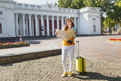 Joyful traveler tourist woman in yellow summer casual clothes, hat with suitcase looking on city map search route in. City outdoor. Girl traveling abroad on royalty free stock photography