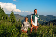 Joyful travelers: a man and a boy are standing on a alpine meado. Joyful travelers: a men and a boy, smiling, are standing amidst lush grass on a alpine meadow Stock Photography