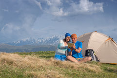 Joyful travelers sit next to tent use tablet and having fun Stock Image