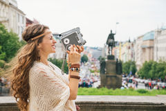 Joyful trendy hippie woman tourist with retro camera in Prague Royalty Free Stock Photography