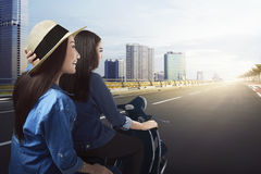 Joyful two asian girls traveling by scooter. With a view of the city Stock Image