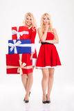Joyful and unhappy blonde sisters twins sharing gifts Stock Images