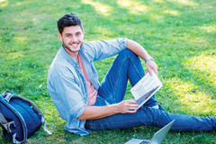 Joyful university life. Cute male student holding a book and loo. King at the camera while sitting on the grass near the campus of the University at the break Stock Photos