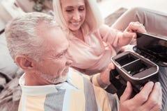 Joyful unshaken man holding and examining the gadget. Its not so hard. Joyful unshaken aged men sitting on the sofa near his wife holding and examining the Stock Photos