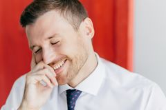 Joyful unshaven male with happy expression, giggles at funny joke, closes eyes with pleasure, dressed in elegant white shirt, reci royalty free stock photos