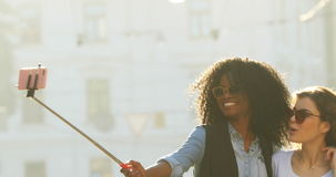 Joyful walk of two smiling multiethnic girlfriends with sunglasses taking photos using the selfie stick. stock footage