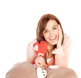 Joyful woman. Image of lovely joyful woman sitting down and covered blanket with red handmade heart-shaped soft toy, isolated on white background, playful facial Stock Photo