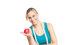 Joyful woman with an apple and a measuring tape. Standing against a white background Royalty Free Stock Images