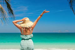 Joyful woman with arm up on beach in summer during holidays travel. Joyful woman with arm up on beach is enjoying serene ocean nature in summer during holidays royalty free stock images