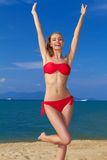Joyful woman with arms raised. Joyful woman in red bikini with arms raised posing by the sea Stock Image