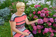 The joyful woman of average years has a rest in a garden near a Stock Photography