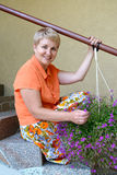 The joyful woman of average years sits on a ladder with decorative flowers a lobelia Royalty Free Stock Image
