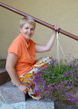 The joyful woman of average years sits on a ladder with decorative flowers a lobelia Stock Images
