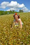 The joyful woman of average years with a wreath on the head in te blossoming buckwheat field Stock Images