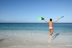 Joyful woman in bikini runs to the sea Stock Photos