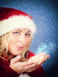 Joyful woman blowing stars in red santa claus hat Stock Photography