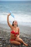 Joyful woman with bottle is sitting on coast Stock Image