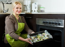 Joyful woman cooking fish. In oven at home kitchen Stock Photo