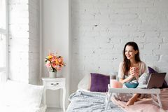Joyful woman with cup of coffee in bed Stock Photo