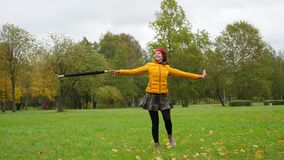 Joyful woman dancing and spinning on field in bright autumn park. Happy girl injoy life and bright fall stock video footage